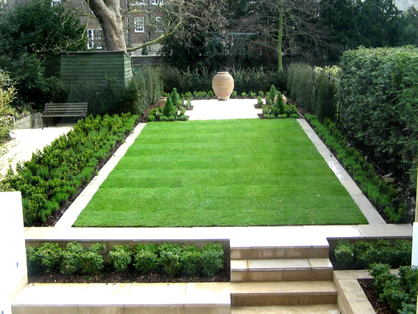 Formal contemporary green garden with perfect lawn edged in ...